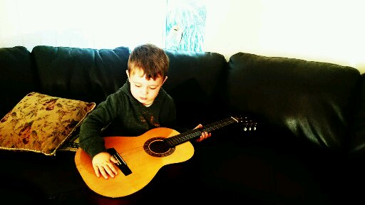 My grandson picked up this guitar and placed it on his knee and started strumming just like his dad at that age :)